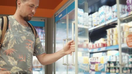 yoghurt : Male visitor of supermarket is looking on racks with milk products. He is opening doors and taking yogurt, putting it in his trolley Stock Footage