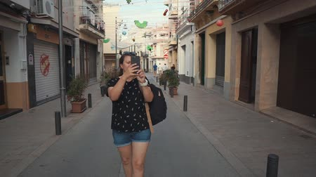 dojem : Tourist woman is taking photo y camera of mobile phone on old city street. She is admiring architecture and capturing her impressions Dostupné videozáznamy