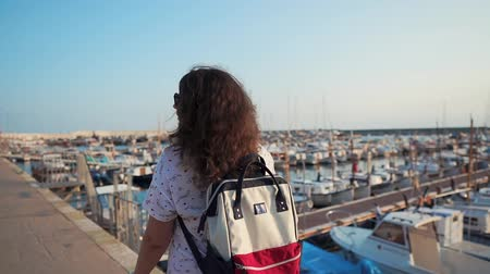 podróżnik : Rear view of charming brunette female tourist with backpack enjoying walk in port, hundreds of yachts and boats. Woman on vacation, viewing harbour in evening.
