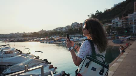 hayran olmak : Adult woman is admiring view of bay with moored yachts in city in sunny day. She is holding mobile phone in hands and trying to take a photo