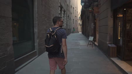 stopping : Bearded male tourist is viewing medieval architecture and small shops in Gothic Quarter of Barcelona. He is strolling alone in daytime, back view