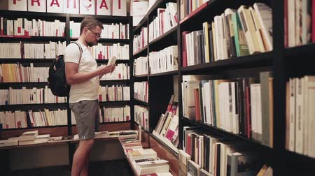 knihkupectví : Side view shot of a casual guy choosing new book in a bookstore. Man taking book from a shelf and read a little. Dostupné videozáznamy