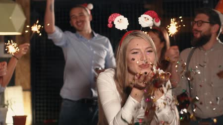 мишура : Young woman is blowing away shiny tinsel from hands on Christmas party. Her friends are jumping and cheering behind her