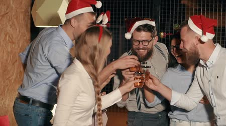 hat : Young male and female companions are cheering and drinking alcohol in Christmas party in evening. One of them is saying toast and clinking glasses together