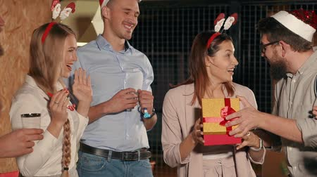 cin cin : Cheerful girl is looking inside a gift box and smiling, embracing her friends on Christmas party. Company of young men and women are celebrating holidays