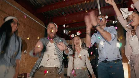 kutluyor : Friends are celebrating Christmas and New year together on a gathering. They are tossing up shiny confetti an dancing in holiday night Stok Video