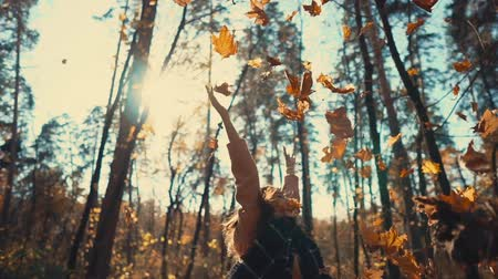 gooien : Cute happy girl is rejoicing by sunny fall day and throwing leaves. She is spinning around herself and smiling broadly, enjoying holidays