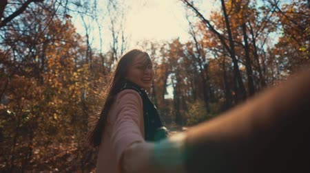 pull out : Cheerful woman is running in sunny fall day in park and stretching hand of her boyfriend. Man is filming her cute and joyful face and his hand in frame