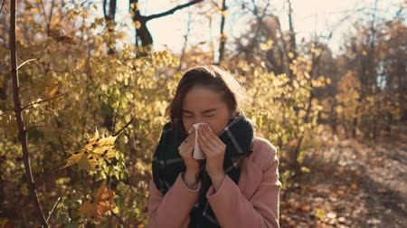 zsebkendő : Pretty girl is caught cold and sneezing during walk in forest in autumn day. She is wrapped in warm scarf, holding hanky and wiping her nose