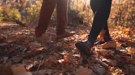 their : Man and woman are dancing and jumping in woodland in fall day. Close-up of their feet and shoes, dried leaves are flying from ground