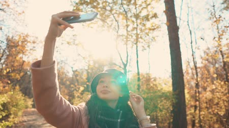 zálesí : Funny woman is photographing her face by smartphone in fall woodland. She is looking at camera of gadget and playing with her black hat