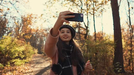 grimacing : Funny young woman is taking selfies by modern mobile phone in fall day in forest. She is smiling, grimacing and correcting her hat, posing