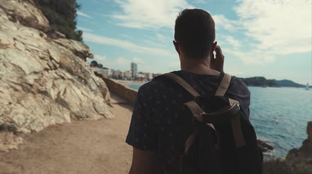 uscire : Man tourist is leaving dark tunnel and walking on path with bright sunny light, back view. He is admiring sea view and panorama of resort city in distance
