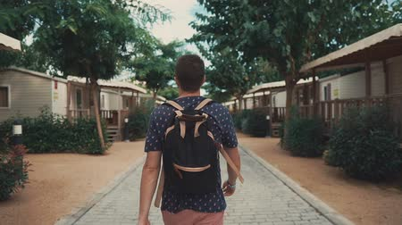 stepping : Tourist man is walking alone on road between little living cottages in resort area, back view. Picturesque and calm territory with bungalows Stock Footage