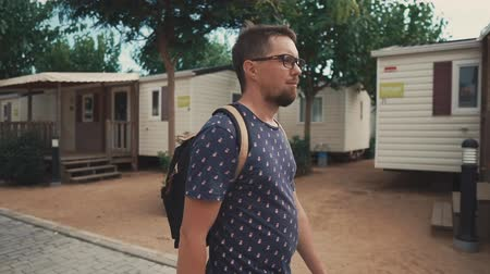 grimacing : Male tourist is walking alone in empty resort area with summer houses. He is grimacing by sunlight and looking around Stock Footage