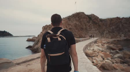 descobrir : Traveler with backpack enjoying lonely walk on the seashore in light summer clothes. Giant rocks on the shore, beautiful nature view. Places for camping.