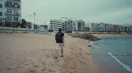backpacken : Tourist with backpack taking a long stroll along the shore in the evening on summer vacation. View on the city and mountains. Stockvideo