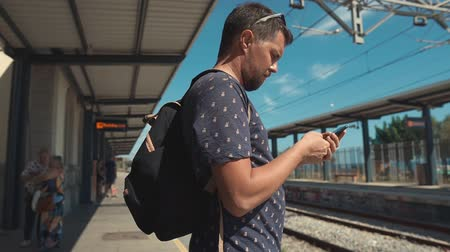 уведомление : Side view shot of a male tourist with bag texting sms on smartphone at train station while waiting for a train. Man traveling.