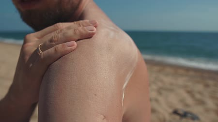 излучение : Adult man is tanning on a seacoast in summer day and covering his skin by sunscreen. He is stroking his shoulder, spreading cream, close-up of his hand