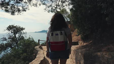 bonne aventure : Female traveler is walking alone on path on mountain and looking on sea from top. She is carrying small backpack, enjoying good weather, back view Vidéos Libres De Droits