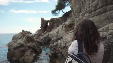 surpreendente : Female tourist is taking pictures of amazing seascape and hard rocks by smartphone. She is using application for photographing, standing in natural landmarks area