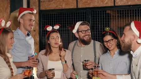 harcama : Many people standing together with drinks and making a toast at christmas party. People in dresses and costumes spending great time on party.