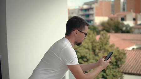 handrails : Young man is resting in terrace and using mobile phone, looking on display. He is leaning on handrails and scrolling touchscreen Stock Footage