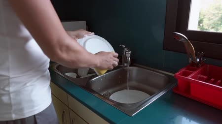 higiênico : Single man is cleaning tableware in daytime in kitchen. He is wiping it by washcloth and removing by water, close-up of hands