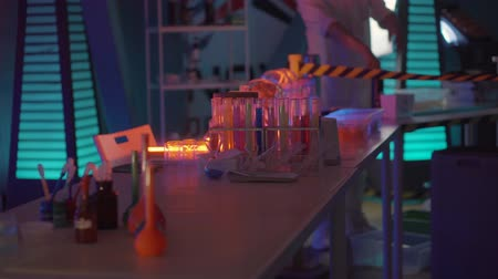 químico : Inside secret scientific laboratory, table with ampoules and reagents. Scientist is standing in distance and performing experiment