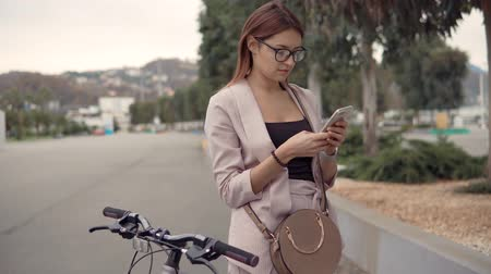 clique : Pretty woman is sending messages by smartphone outdoors. She is resting in park, standing near her bicycle Stock Footage