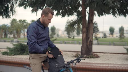 movimentar se : Young male cyclist is putting tablet inside bag and moving out in city. City dweller is using contemporary ecological transport