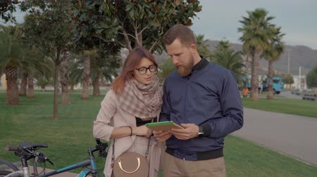 gesticulando : Pair of guy and girl are talking about routs for bicycle walking in park. They are looking at display of tablet with map, bikes are near Vídeos
