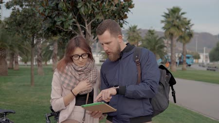 sobre : Young man and woman are watching on screen of tablet and discussing routes of park area. They are gesticulating and talking to each other