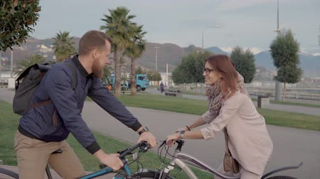 saying : Male and female friends are farewelling in park and keeping driving bikes. They are hitting on hands and smiling