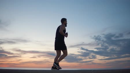 tutmak : Sportsman is jogging in evening time, view of his figure in background of picturesque clouds in sky. Man is working out, using healthy lifestyle and keeping fit Stok Video