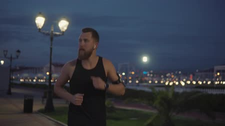 fitness tracker : Handsome bearded man is running in marathon in evening time in darkness. He is viewing on his smartwatch with fitness tracker, close-up