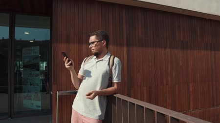 gastos : Side view of a causal guy in glasses wearing backpack standing by the building with a smartphone. Boring day, killing time online on smartphone.