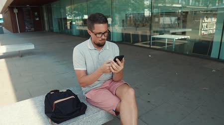 matança : Urban guy sitting on a bench by the building in summertime and texting on smartphone, killing time alone. Tourist with backpack holding a gadget.