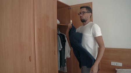 traje de passeio : Guy in glasses choosing decent shirt to go out in city, dressing for a walk. Mans wardrobe. Stock Footage