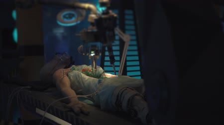 экспонат : UFO exhibtion: Cut open alien on operating table connected to machines. Robot hands performing surgery. Стоковые видеозаписи