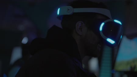 ハイテック : Happy and excited man wearing futuristic looking VR goggles. Virtual reality games. Man playing games in VR goggles in a dark room with blue light. 動画素材