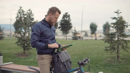 sırt çantasıyla : Guy using his tablet to check fitness goals in app. Man using gadget outdoor on a bike ride.