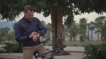 байкер : Man makes a stop during bike ride to check messages on a smartwatch. Progressive man using smart gadget on a ride. Стоковые видеозаписи