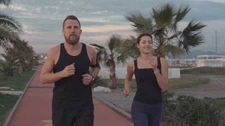 spare : Fitness couple jogging in the evening together in park. Happy active couple talking while running. Stock Footage