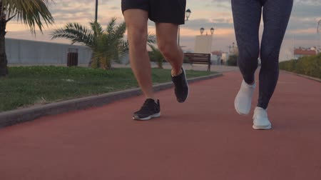 casal : Close-up shot of a mans and womans legs while they running side by side. Active lifestyle. Sport couple wearing sportswear.