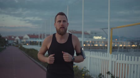 cross training : Portrait of a handsome bearded guy jogging outdoor on the shore. Active man in black tank top running in earphones. Stock Footage