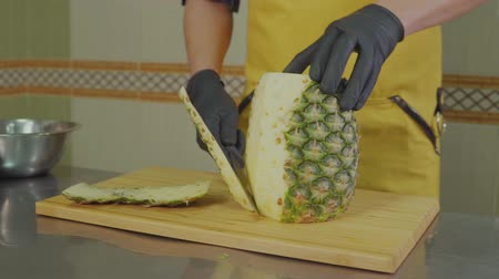 bilenmiş : Man is cutting peel of exotic fruit pineapple on wooden cutting board. He is working on professional kitchen, close-up of hands Stok Video