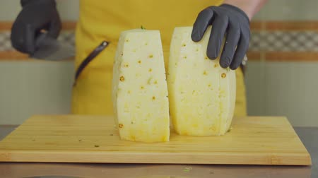 yarık : Male cook is cutting juicy pineapple on chopping board in kitchen. He is slicing it by half and removing hard core