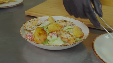kendi : Chef is decorating his signature salad by fried pineapple pieces. He is cooking fusion style meals in luxury restaurant, close-up view of hands