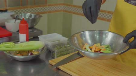 olive oil pour : Chef man is cooking useful and low-calorie vegan salad with vegetables. He is adding herbs, salt, spices and olive oil, close-up Stock Footage